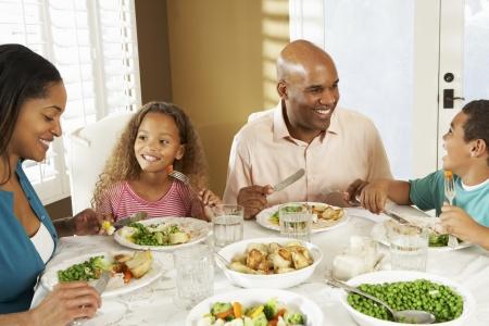 familia comiendo: Familia Disfrutando comida en casa Foto de archivo