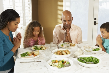 5 10 year old girl: Family Saying Grace Before Meal At Home