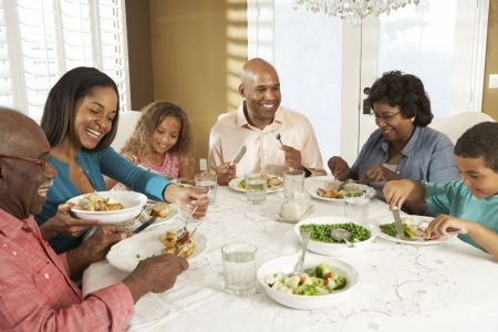 Multi Generation Family Enjoying Meal At Home Stock Photo