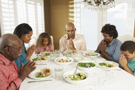 5 10 year old girl: Multi Generation Family Saying Grace Before Meal At Home