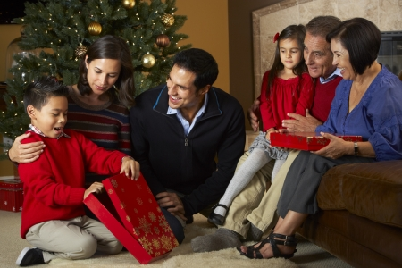 5 10 year old girl: Multi Generation Family Opening Christmas Presents In Front Of Tree Stock Photo