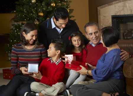 5 year old girl: Multi Generation Family Opening Christmas Presents In Front Of Tree Stock Photo