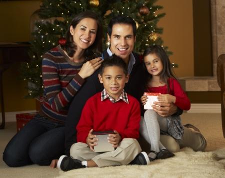 nios hispanos: Familia delante del �rbol de navidad Foto de archivo
