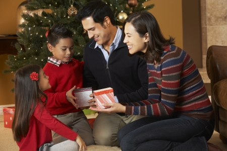 unwrapping: Family Opening Presents In Front Of Christmas Tree Stock Photo
