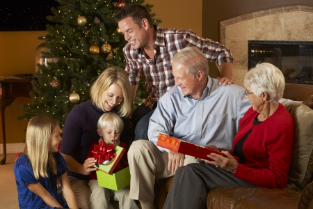 18 to 30s: Multi Generation Family Opening Christmas Presents In Front Of Tree Stock Photo