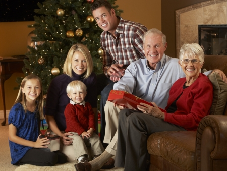 six month old: Multi Generation Family Opening Christmas Presents In Front Of Tree Stock Photo
