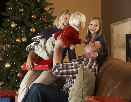 Family Opening Presents In Front Of Christmas Tree Stock Photo