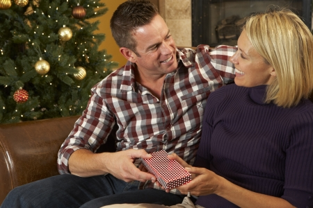Couple Opening Presents In Front Of Christmas Tree photo