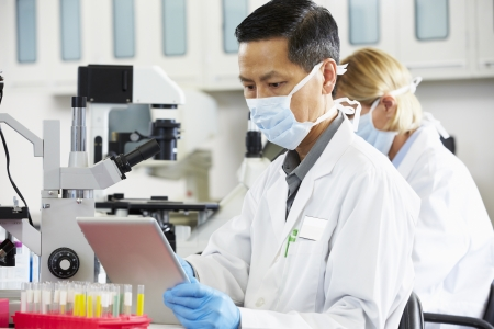 scientist woman: Male Scientist Using Tablet Computer In Laboratory Stock Photo