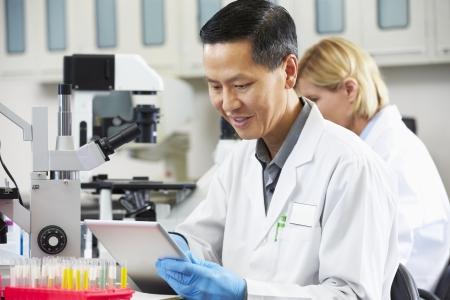 bata de laboratorio: Cient�fico Hombre Usar el ordenador Tablet En Laboratorio Foto de archivo
