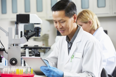 scientist: Male Scientist Using Tablet Computer In Laboratory Stock Photo