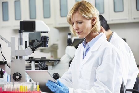 biologist: Female Scientist Using Tablet Computer In Laboratory