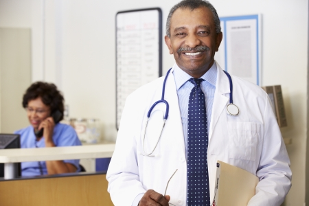 smiling female doctor: Portrait Of Doctor At Nurses Station Stock Photo