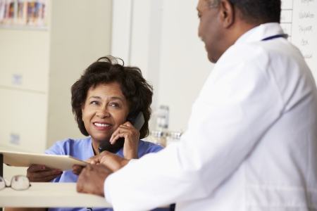 nurse station: Doctor In Discussion With Nurse At Nurses Station