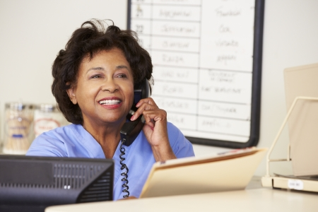 nurse computer: Nurse Making Phone Call At Nurses Station Stock Photo