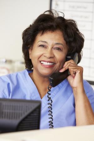 nurses station: Nurse Making Phone Call At Nurses Station Stock Photo