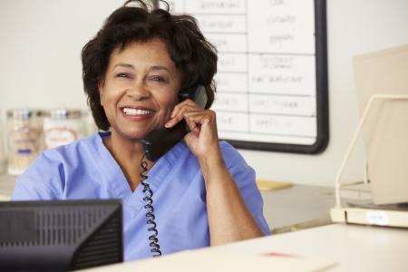 nurse computer: Nurse Making Phone Call At Nurses Station Stock Photo