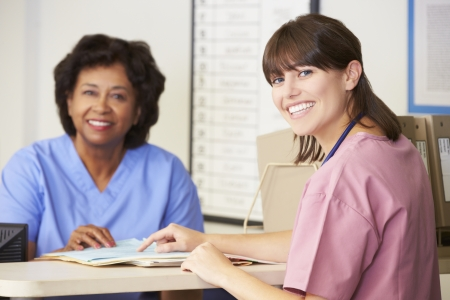 nurses station: Two Nurses In Discussion At Nurses Station