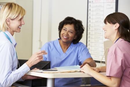 amigas conversando: Doctor Y Enfermeras En La Discusión En la estación de enfermeras