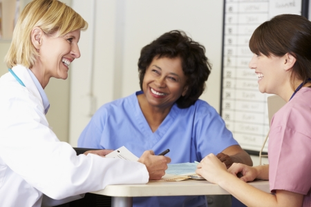 Doctor And Nurses In Discussion At Nurses Station photo