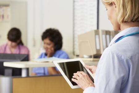nurses station: Female Doctor Using Digital Tablet At Nurses Station