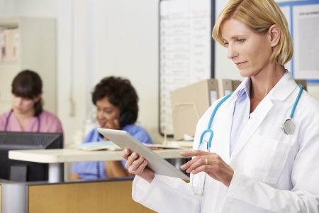Female Doctor Using Digital Tablet At Nurses Station photo