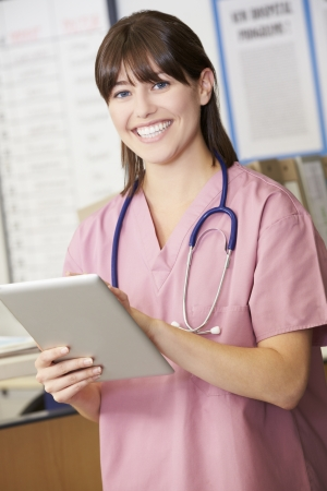 nurse station: Nurse Using Digital Tablet At Nurses Station Stock Photo