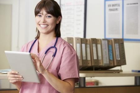 enfermera con paciente: Enfermera que usa la tablilla digital En la estación de enfermeras