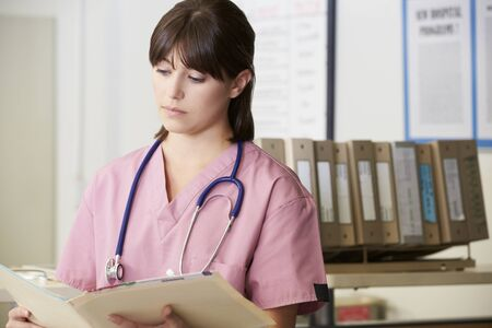 Nurse Reading Patient Notes At Nurses Station photo