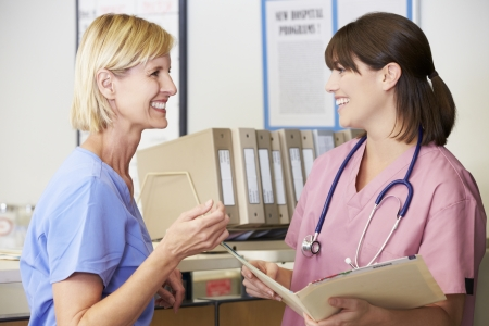 nurse station: Two Nurses Discussing Patient Notes At Nurses Station Stock Photo