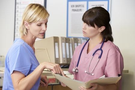nurse station: Two Nurses Discussing Patient Notes At Nurses Station Stock Photo