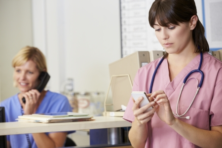 Nurse Using Mobile Phone At Nurses Station photo