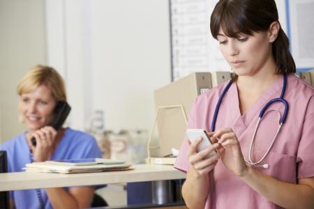 nurses station: Nurse Using Mobile Phone At Nurses Station Stock Photo