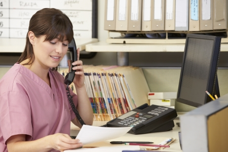 nurse station: Nurse Making Phone Call At Nurses Station Stock Photo