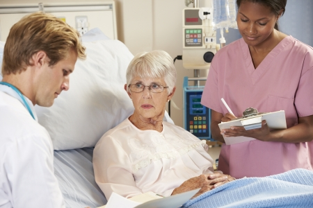hospital notes: Doctor With Nurse Talking To Senior Female Patient In Bed