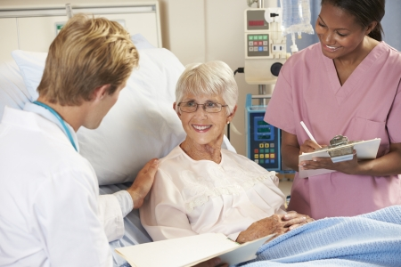 happy doctor woman: Doctor With Nurse Talking To Senior Female Patient In Bed