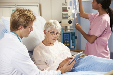 Doctor Using Digital Tablet In Consultation With Senior Female Patient In Bed photo