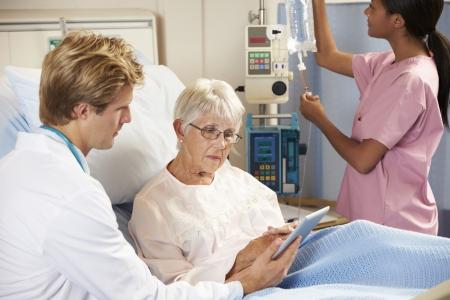 recovery bed: Medico con tavoletta digitale in consultazione con senior paziente a letto