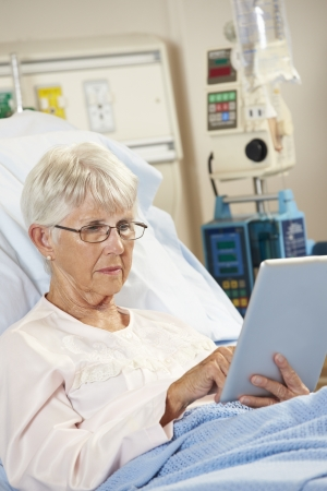 Senior Female Patient Relaxing In Hospital Bed With Digital Tablet photo