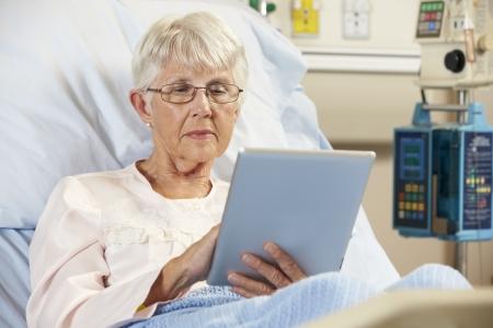 malade au lit: Patient senior de d�tente dans son lit d'h�pital avec tablette num�rique