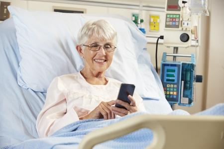 recovery bed: Senior paziente in ospedale Usare il telefono cellulare