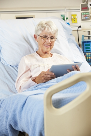 e book reader: Senior Female Patient Relaxing In Hospital Bed With Digital Tablet