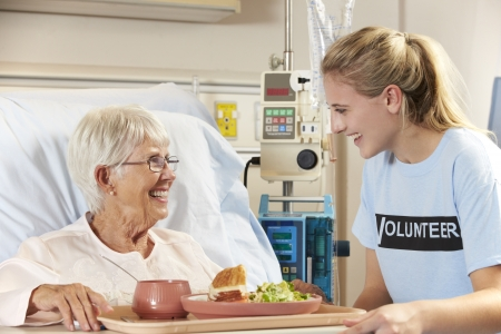 healthcare visitor: Teenage Volunteer Serving Senior Female Patient Meal In Hospital Bed Stock Photo