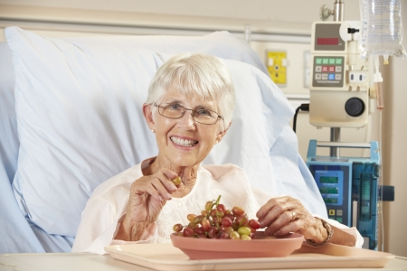 Senior Female Patient Eating Grapes In Hospital Bed photo