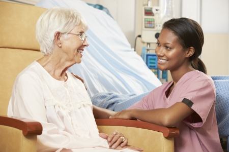 patient: Nurse Talking To Senior Female Patient Seated In Chair By Hospital Bed