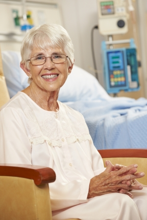 geriatric care: Portrait Of Senior Female Patient Seated In Chair By Hospital Bed