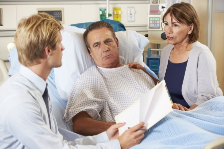 homme inquiet: Doctor Talking To Couple Sur Ward