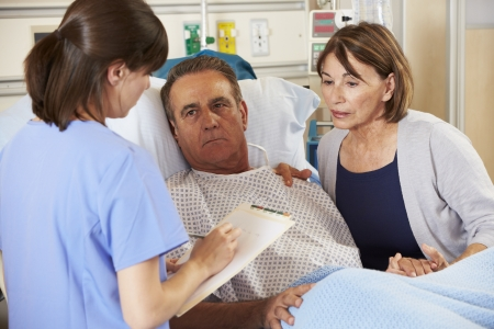 sick in bed: Nurse Talking To Couple On Ward Stock Photo