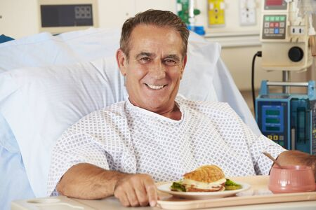 Male Patient Enjoying Meal In Hospital Bed photo