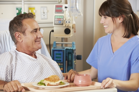 Patient Being Served Meal In Hospital Bed By Nurse photo